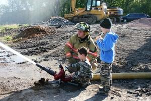 Fireman helps kids use firehose